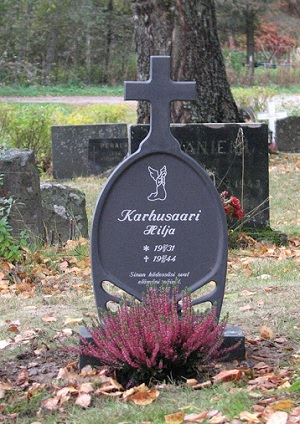 Valettu hautaristi hautakivien joukossa.