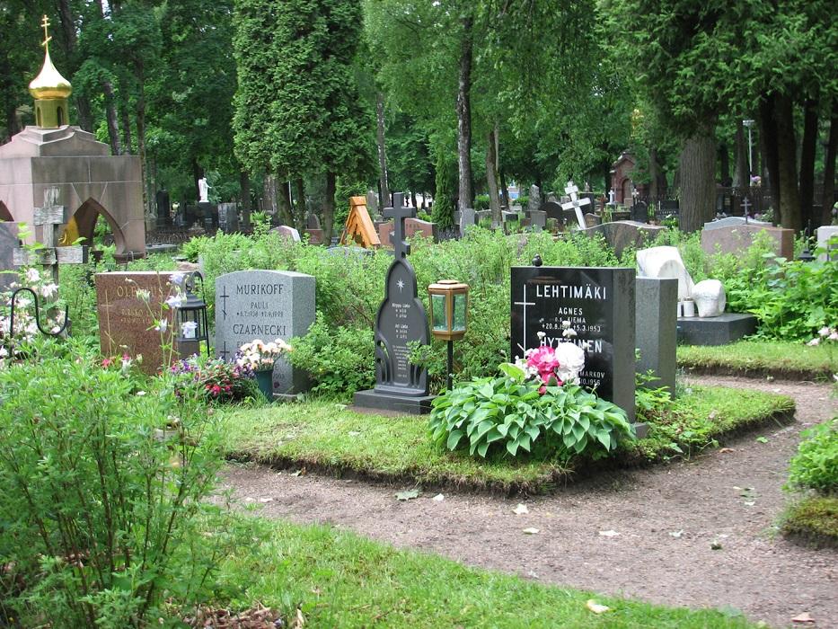 Ortodoksiristi hautausmaalla hautakivien ja puuristien joukossa.